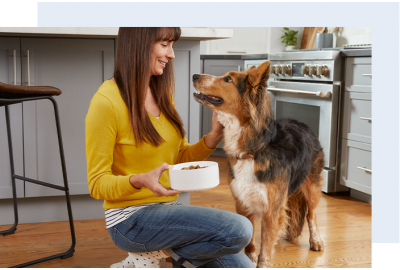 Young Woman Feeding Her Dog Bowl of Kibble
